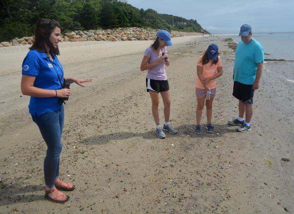 Crystal shares facts about the young horseshoe crab at the feet of a visiting family