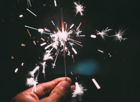 Hand holding a celebratory sparkler