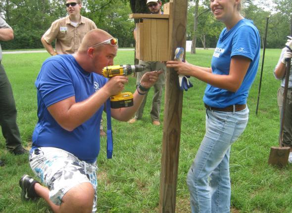 Tyler and Erica screwing the birdbox onto the post