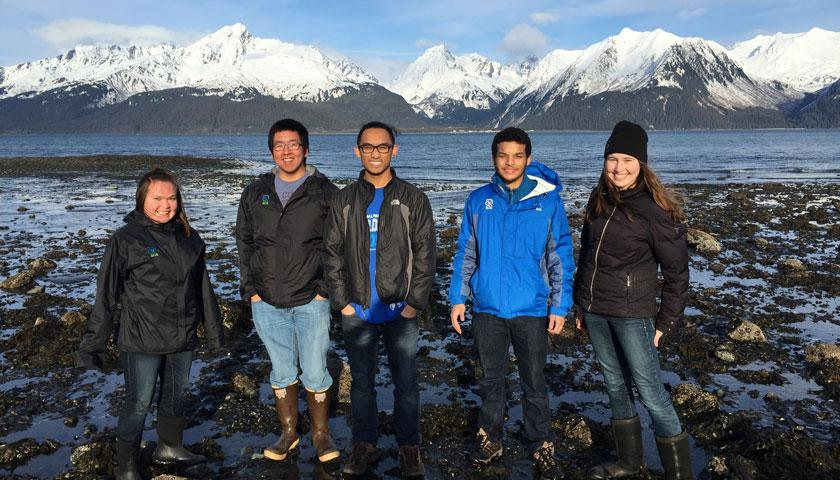 Members of SCA's Alaska National Park Service Academy standing before a snow-capped mountain range in Alaska