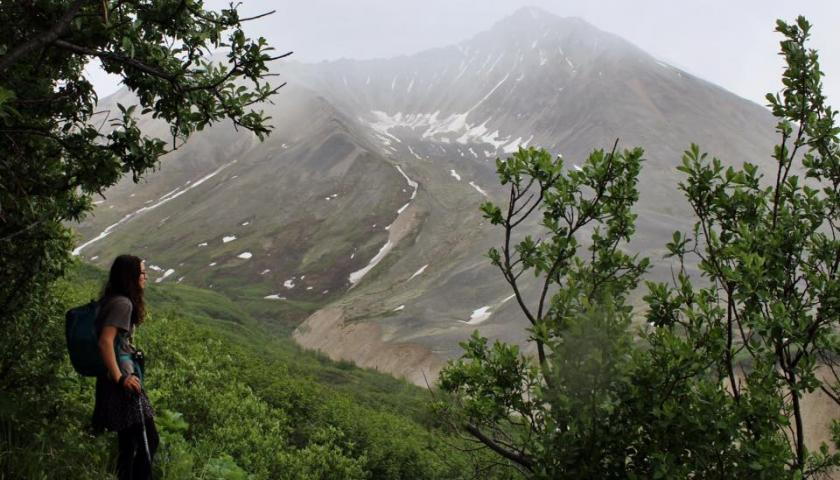 SCA Intern Montana Napier overlooks Wrangell-St. Elias National Park in Alaska through the haze of a wildfire