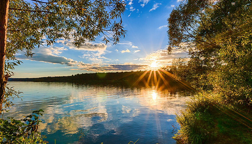 Scenic view of beautiful sunset above the river at summer evening.