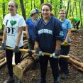 Girl Scouts Katherine, Ellie, Phoebe and Crew Leader Cat Cook carrying a debarked log down to the work site.